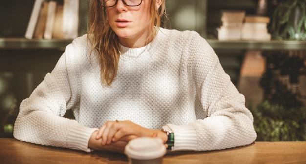 Femme blonde prenant une tasse de café