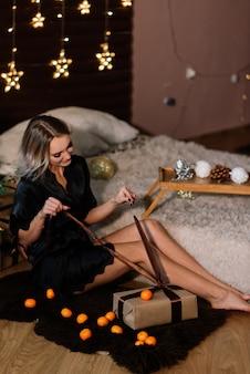 Femme blonde près de sapin pour la célébration du nouvel an et de noël.