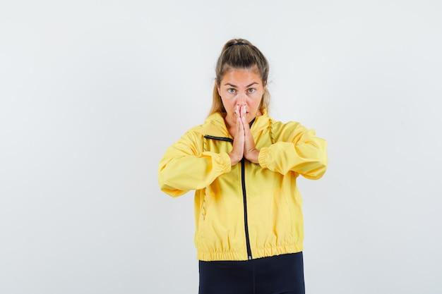 Femme blonde priant en blouson aviateur jaune et pantalon noir et à la recherche concentrée
