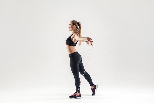 Femme blonde de profil, tenant la corde à sauter. prise de vue en studio, fond gris