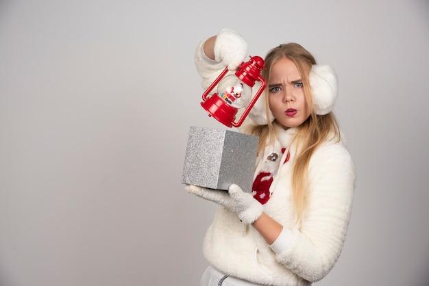 Femme blonde en pull blanc montrant son cadeau.