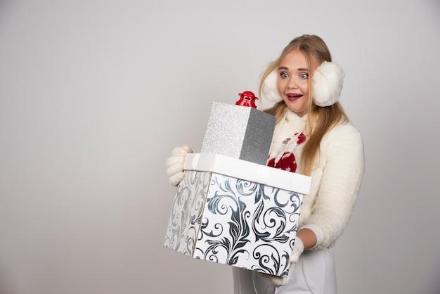 Femme blonde en pull blanc regardant les cadeaux de noël.