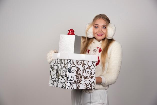Femme blonde en pull blanc tenant des cadeaux de noël.