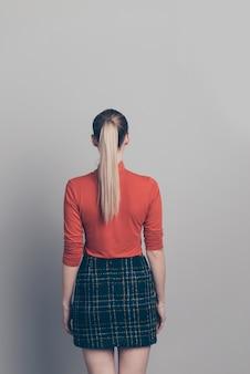 Femme blonde avec un pull à col roulé rouge posant contre le mur gris