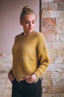 Femme blonde en pull jaune cool