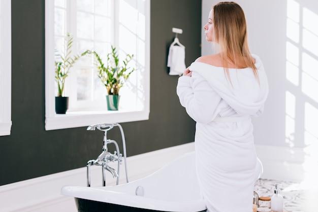 Femme blonde qui pose dans la salle de bain avec un peignoir