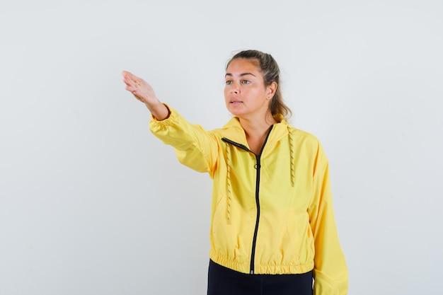Femme blonde qui tend la main vers la gauche en blouson aviateur jaune et pantalon noir et à la sérieuse