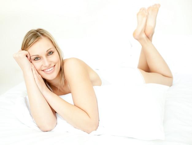 Femme blonde radiante, allongée sur le lit