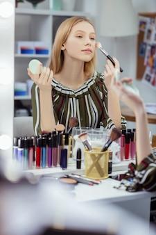 Femme blonde ravie se regardant tout en profitant de sa beauté