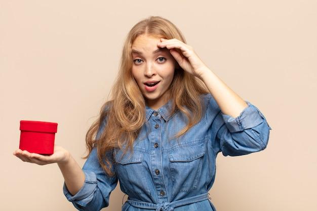 Femme blonde à la recherche de bonheur, étonné et surpris, souriant et réalisant une bonne nouvelle incroyable et incroyable