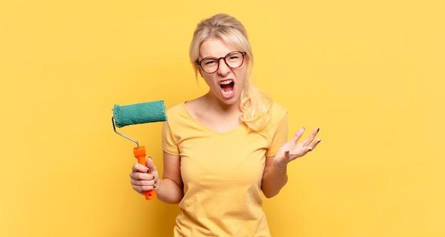 Femme blonde à la recherche de colère, agacée et frustrée hurlant wtf ou quel est le problème avec vous