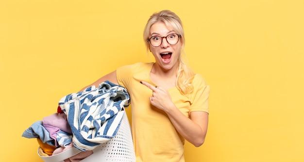 Femme blonde à la recherche excitée et surprise en pointant vers le côté et vers le haut pour copier l'espace
