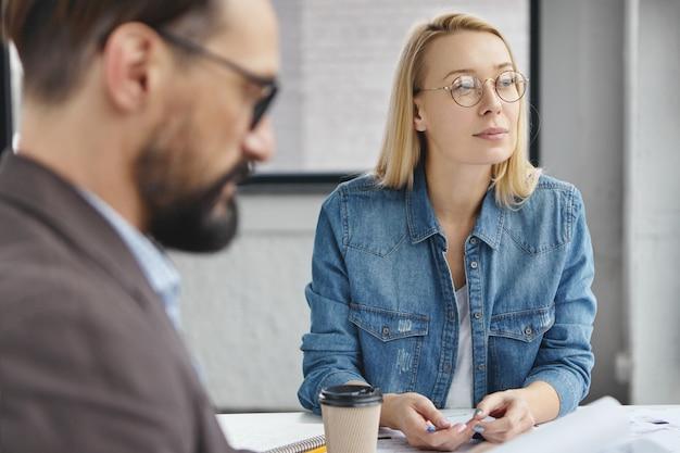 Femme blonde réfléchie est assise avec son patron
