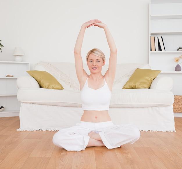 Femme blonde en regardant la caméra tout en faisant des exercices de fitness