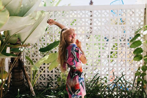 Femme blonde regardant par-dessus l'épaule et riant sur fond de nature.