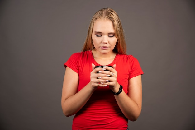 Femme blonde regardant une tasse de thé sur un mur noir.