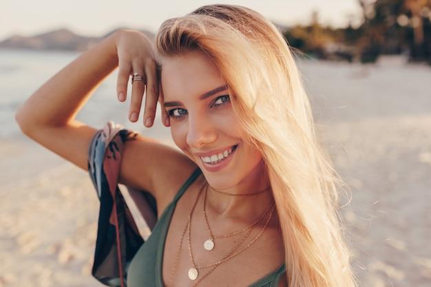 Femme blonde rêveuse posant sur la plage