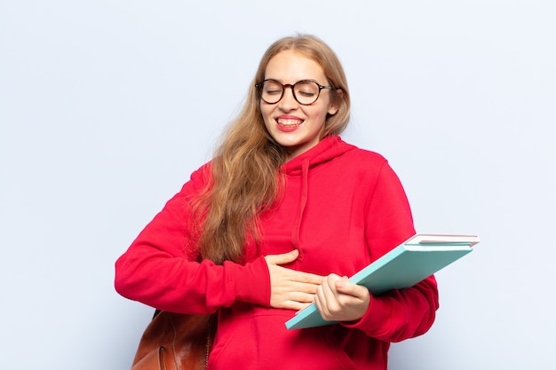 Femme blonde riant aux éclats d'une blague hilarante, se sentant heureuse et joyeuse, s'amusant