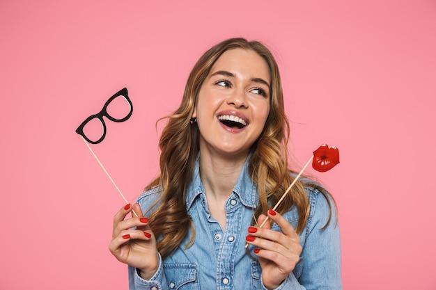 Femme blonde riante vêtue d'une chemise en jean posant avec de fausses lèvres et des lunettes tout en détournant les yeux par-dessus le mur rose