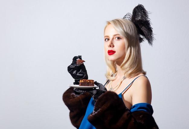 Femme blonde en robe bleue vintage et manteau de fourrure avec gâteau