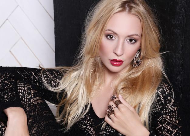 Femme blonde en robe en dentelle noire