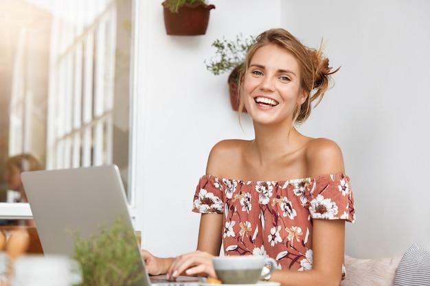Femme blonde en robe à fleurs au café