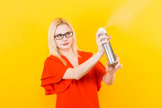 Femme blonde en robe avec pulvérisateur