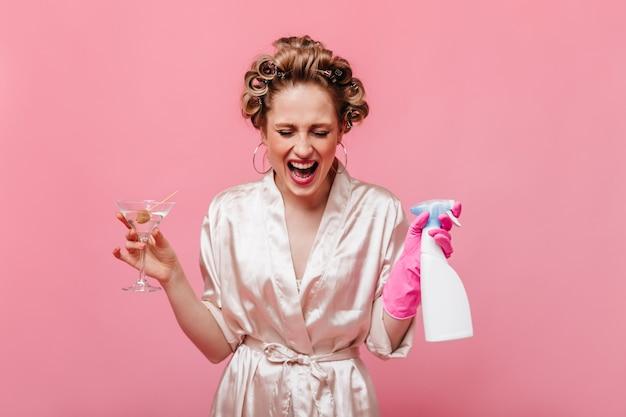 Femme blonde en robe rose pose avec verre à martini et détergent