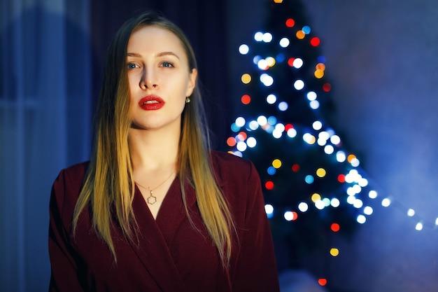 Femme blonde en robe rouge contre l'arbre de noël à la maison. décorations du nouvel an