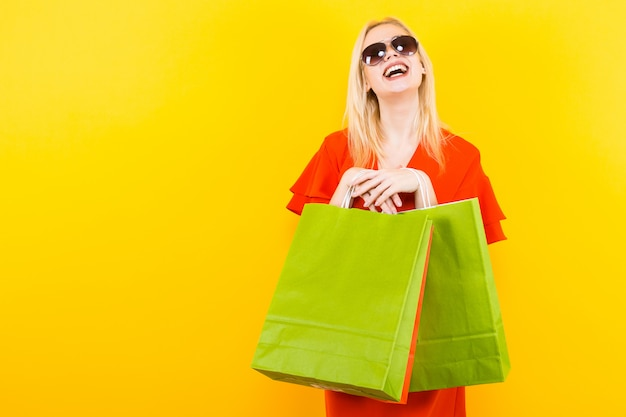 Femme blonde en robe avec des sacs
