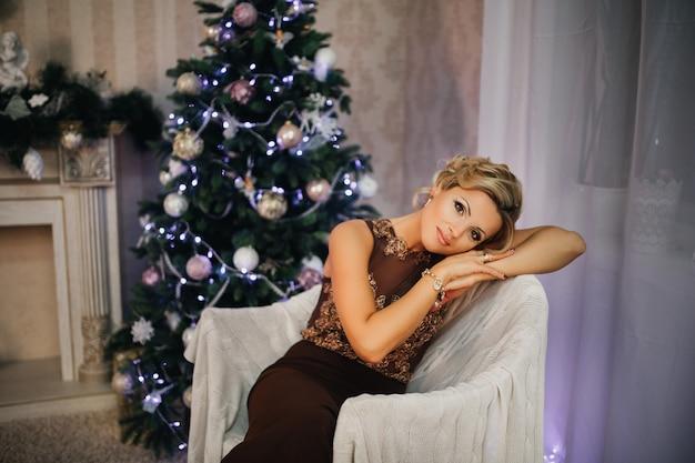 Femme blonde en robe de soirée longue assise sur le fond de l'arbre de noël