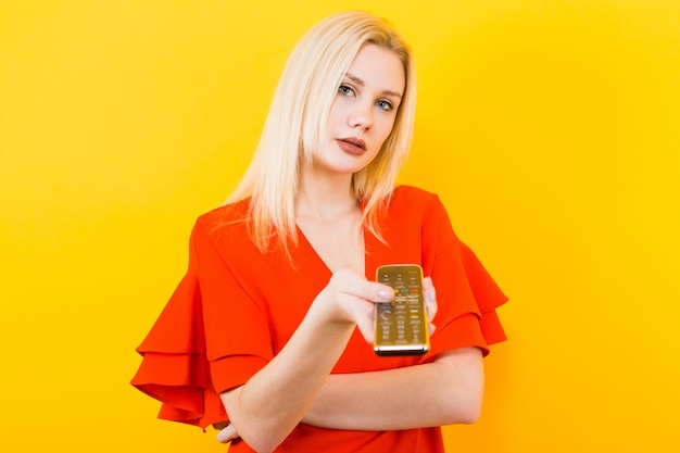 Femme blonde en robe avec télécommande