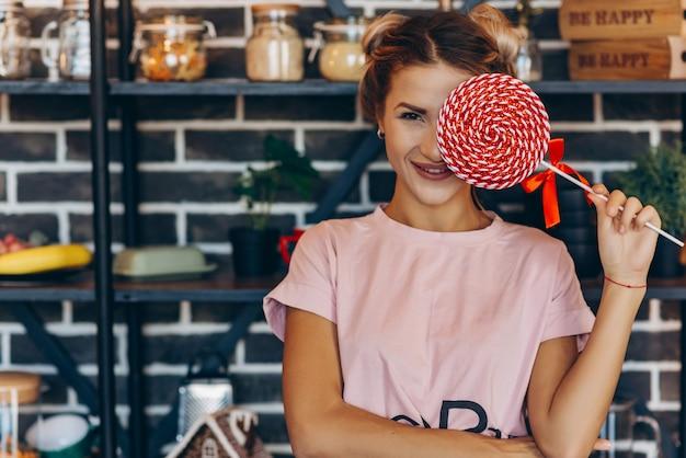 Femme blonde en rose avec une grosse sucette dans les mains