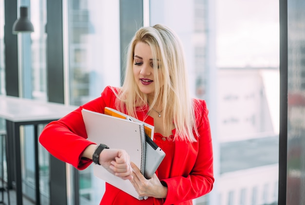 Une femme blonde en rouge regardant sur sa montre