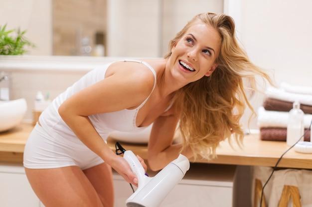 Femme blonde s'amuse pendant le séchage des cheveux dans la salle de bain