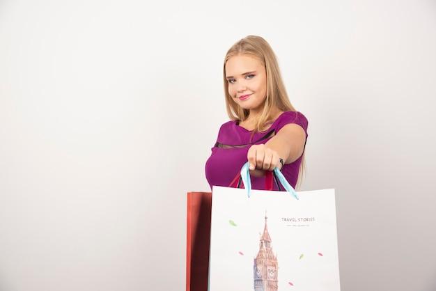 Femme blonde avec des sacs à provisions posant.