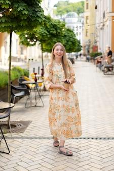 Une femme blonde satisfaite de race blanche vêtue d'une robe boit du café à emporter et marche dans la rue sur fond d'arbres verts en été