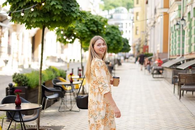 Une femme blonde satisfaite de race blanche vêtue d'une robe boit du café à emporter et marche dans la rue sur fond d'arbres verts et de lanternes jaunes