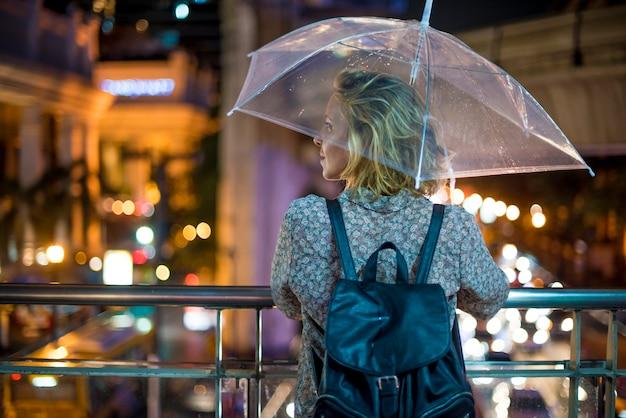 Femme blonde se mettant à l'abri sous son parapluie