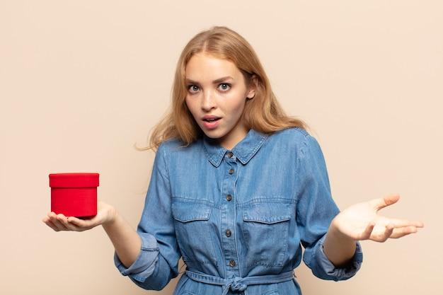 Femme blonde se sentant extrêmement choquée et surprise, anxieuse et paniquée, avec un regard stressé et horrifié