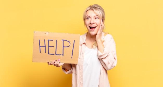 Femme blonde se sentant heureuse, excitée et surprise, regardant sur le côté avec les deux mains sur le visage