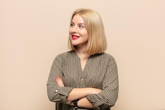 Femme blonde se sentant heureuse, fière et pleine d'espoir, se demandant ou pensant