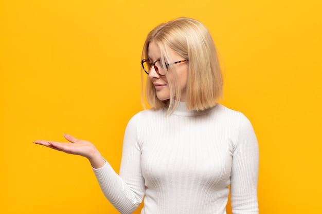 Femme blonde se sentant heureuse et souriante avec désinvolture, regardant un objet ou un concept tenu sur la main sur le côté