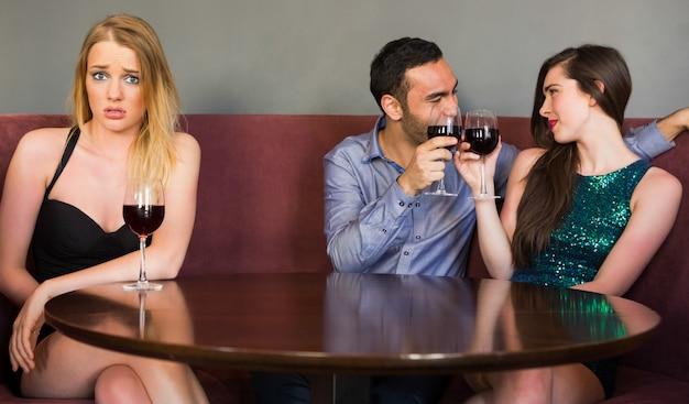 Femme blonde se sentant jalouse comme deux personnes flirtent à côté d'elle