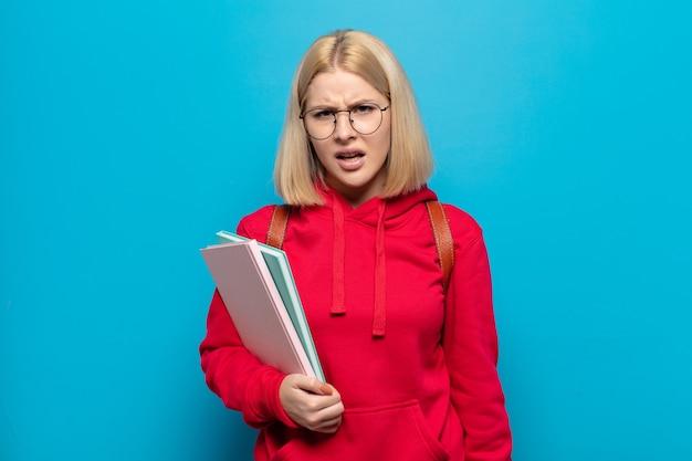 Femme blonde se sentant perplexe et confuse, avec une expression stupide et abasourdie en regardant quelque chose d'inattendu