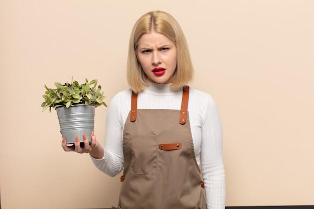 Femme blonde se sentant perplexe et confuse, avec une expression stupide et stupéfaite en regardant quelque chose d'inattendu