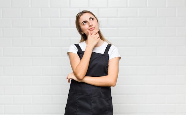 Femme blonde se sentant réfléchie, se demandant ou imaginant des idées, rêvassant et levant pour copier l'espace