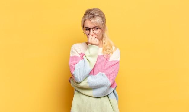 Femme blonde se sentant sérieuse, réfléchie et inquiète, regardant de côté avec la main pressée contre le menton