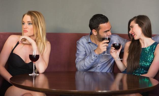 Femme blonde se sentant seule comme deux personnes flirtent à côté d'elle