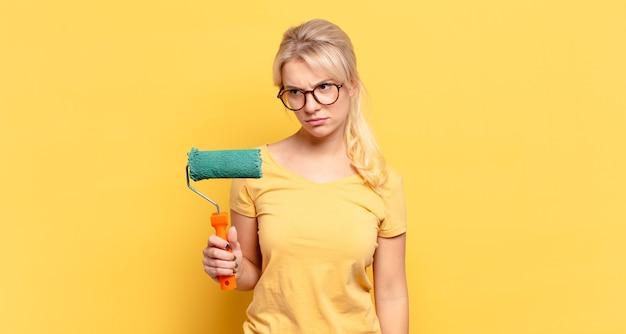 Femme blonde se sentant triste, bouleversée ou en colère et regardant de côté avec une attitude négative, fronçant les sourcils en désaccord